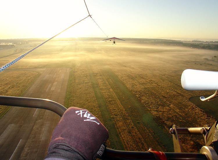 erster Tandemdrachenflug morgens bei leichtem Bodennebel in den Sonnenaufgang. Photo Andreas Ernst Becker